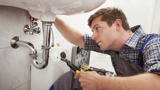 Υδραυλικός επισκευάζει τους σωλήνες του νεροχύτη του μπάνιου
